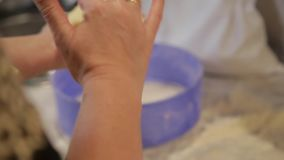 The hostess knead dough for bread. Close up slow motion RAW footage of a woman kneading the dough for a bread in the. HD.The hostess knead dough for bread. Close stock footage