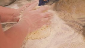 The hostess knead dough for bread. Close up slow motion RAW footage of a woman kneading the dough for a bread in the. HD.The hostess knead dough for bread. Close stock video footage
