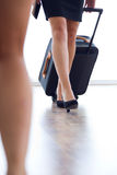 Hostess legs with luggage in airport. Royalty Free Stock Photos
