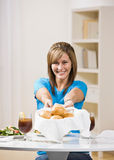 Hostess offering bread roll to guest Stock Image