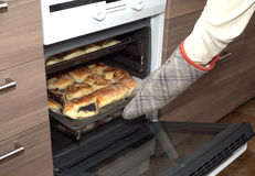 Hostess open oven door and takes bakery from kitchen stove. Side view closeup Royalty Free Stock Photo