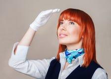 Hostess in uniforme blu e bianca con capelli rossi Immagini Stock Libere da Diritti