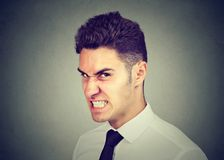 Hostile business man looking at camera with angry face expression. Hostile young business man looking at camera with angry face expression stock image