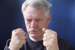 Hostile and combative senior man. Belligerent older man is angry and ready for a fight stock photography
