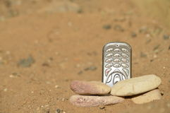 Hostile communication. Close-up view of mobile phone posing with stones on arid, dry and desolate terrain. Concept of remote communication in remote, desolate royalty free stock photos