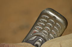 Hostile communication. Close-up view of mobile phone posing with stones on arid, dry and desolate terrain. Concept of remote communication in remote, desolate stock photos