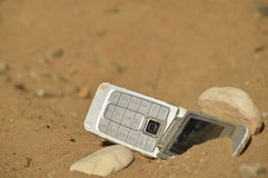 Hostile communication. Close-up view of mobile phone posing with two stones on arid, dry and desolate terrain. Concept of remote communication in remote royalty free stock photo