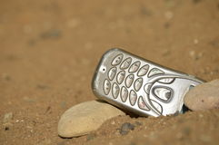 Hostile communication. Close-up view of mobile phone posing with two stones on arid, dry and desolate terrain. Concept of remote communication in remote royalty free stock image