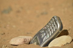 Hostile communication. Close-up view of mobile phone posing with two stones on arid, dry and desolate terrain. Concept of remote communication in remote stock images