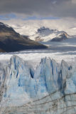 Hostile glacier Perito Moreno with mountain background. The sun giving away a show with clouds lighting up parts of the glacier giving a nice picture royalty free stock images