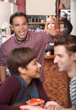 Hostile Man and Loving Couple. Hostile men with raised fist threatening loving couple in cafe royalty free stock photos