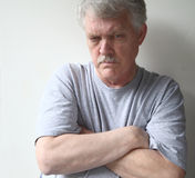 Hostile senior man. Angry older man with his arms crossed stock images