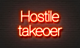 Hostile takeover neon sign on brick wall background. Stock Image