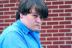 Hostile Teen Boy. Portrait of a teenage boy with a hostile expression. Taken outdoors with brick wall background stock photo