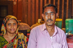 Hosts in Bangladesh. Morolgang, Bangladesh - circa July 2012: Black-haired man with moustache dressed in pink shirt with his wife with colourful headcloth in Stock Photos