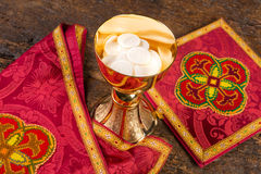 Hosts or wafers in chalice for communion. Communion scene of a chalice with vestment set and wafers Royalty Free Stock Image