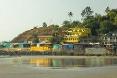 Hotéis amarelos brilhantes em um monte com palmeiras ao lado de um Sandy Beach molhado fotos de stock royalty free