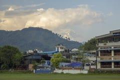 Hotéis das casas contra um monte verde e a parte superior nevado da montagem Annapurna nas nuvens imagens de stock royalty free