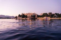 Hotéis nos bancos do udaipur do pichola do lago no crepúsculo Foto de Stock Royalty Free
