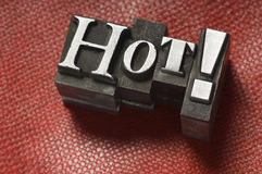 Hot!. The word Hot photographed using vintage letterpress type on a red lizard skin background royalty free stock images