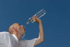 Hot. Young man with a bottle of water Royalty Free Stock Images