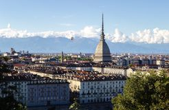 A hot-air ballon flying near the Mole, in a Turin panorama with the alps in background. 