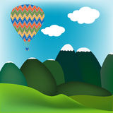 Hot air ballon over a mountain landscape Royalty Free Stock Photo