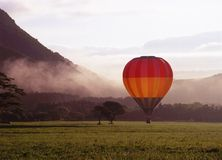 Hot Air Balloon. A colorful hot air ballon landing in a misty morning meadow Royalty Free Stock Photography