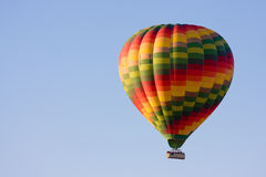 Hot air balloon. Brightly coloured hot air balloon against a clear blue sky royalty free stock image