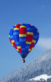 Hot air balloon. A hot-air balloon flying over a chalet in the Swiss alps Royalty Free Stock Image