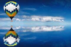 Hot air balloon. On blue sky background reflected in water Royalty Free Stock Image