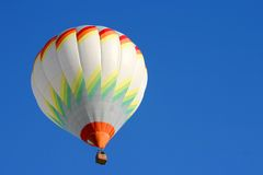 Hot air balloon. In flight isolated on blue sky Royalty Free Stock Photography