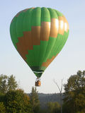 Hot Air Balloon. Green and gold hot air balloon descending into forested area stock photo