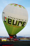 Euro Department - White and Green Hot Air Balloon. White and green hot air balloon - with publicity to Euro Department (french) - on the ground, during ninth royalty free stock photography