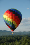 Hot Air Balloon. Colorful hot air balloon soaring in the blue summer sky royalty free stock photo