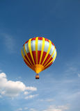 Hot Air Balloon. Yellow and red hot air balloon flying in a blue sky Stock Image