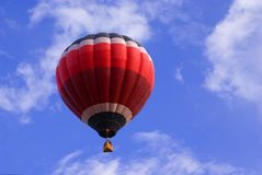 Hot Air Balloon. Colorful Hot Air Balloon in deep blue sky with fluffy clouds Royalty Free Stock Image