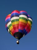 Hot air balloon. Bright colorful hot air balloon taking off into a clear blue sky royalty free stock photos