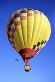 Hot Air Balloon. Bright yellow hot air baloon taking off into a clear blue sky royalty free stock photos