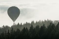 Hot air balloon above the foggy forest Royalty Free Stock Image