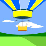 Hot Air Balloon. Above green space with blue sky and clouds in background Stock Illustration