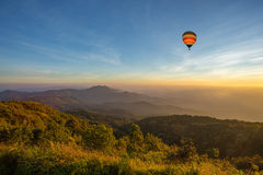 Hot air balloon above high mountain at sunset Stock Photography