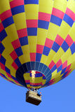 Hot Air Balloon Adventure. Colorful hot air balloon in the sky over the river at the Quechee Vermont Hot Air Balloon Festival firing its propane tanks stock image