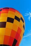 Hot air balloon against blue sky. Colourful yellow, red, black hot air balloon against blue sky Stock Photos