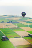 Hot air balloon with agricultural landscape Stock Photos