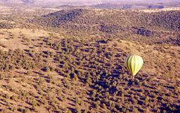 Hot Air Balloon. Ballon floating over desert sands and brush royalty free stock photography