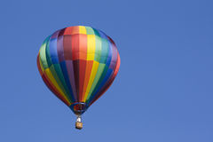 Hot air balloon in the blue sky. A multicolored hot air balloon floats in the blue sky Stock Image