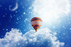 Hot air balloon in blue sky with bright stars and crescent Stock Photos