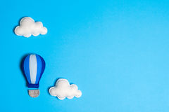 Hot air balloon in blue sky with clouds, copyspace. Hand made felt toys. Royalty Free Stock Photography