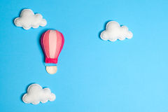 Hot air balloon in blue sky with clouds, frame, copyspace. Hand made felt toys. Abstract sky. Concept for travel agency, motivation, business development stock photos